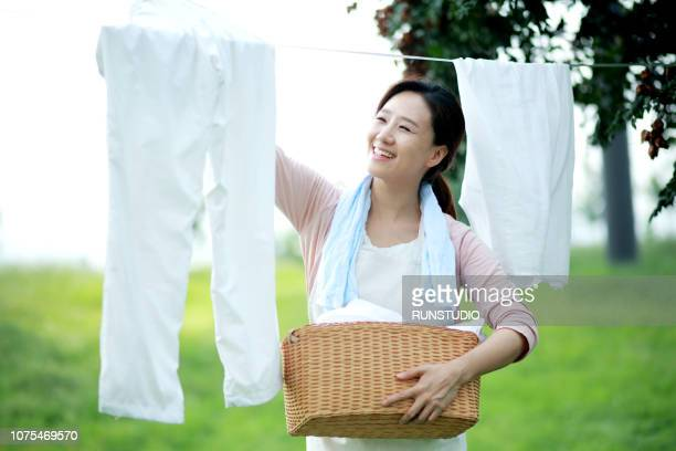 woman hanging laundry outdoors - stereotypical homemaker stock pictures, royalty-free photos & images