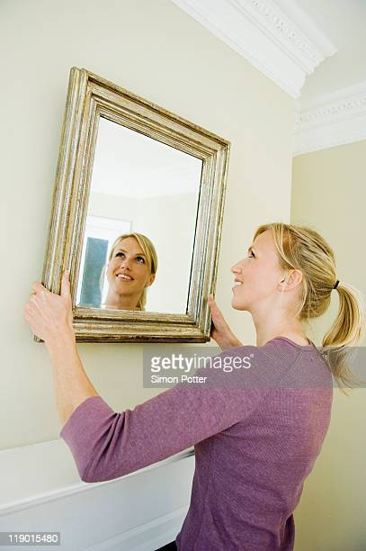 woman hanging mirror on wall - hanging stock pictures, royalty-free photos & images