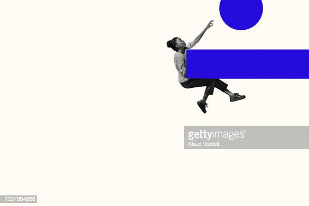 woman hanging on ramp while reaching for circle - at the edge of stock pictures, royalty-free photos & images