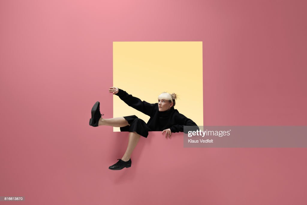 Woman hanging on to square opening in coloured wall, feet dangling : Stock Photo