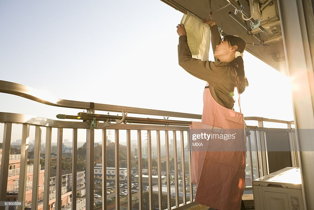 Woman hanging out laundry at balcony : Stock Photo