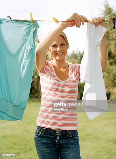 A woman hanging out laundry in a garden.