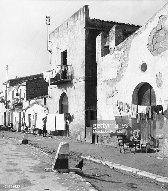 'A woman hanging out the laundry in a street of the city Agrigento December 1956 '
