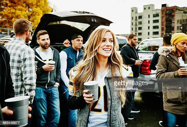 Woman hanging out with friends at tailgating party