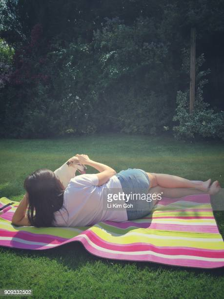 Woman hanging out with her Jack Russell Terrier dog in the garden, England
