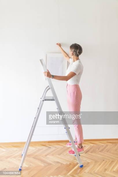 woman hanging painting using ladder - ajustar imagens e fotografias de stock