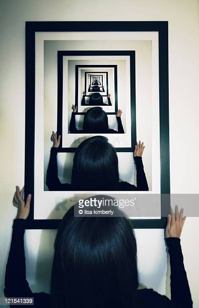 Woman hanging photo on wall with droste effect