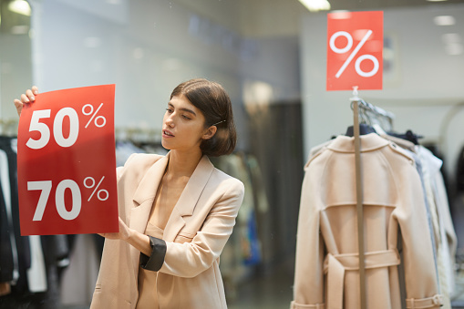 Woman Hanging Sale Signs in Store 1176723601