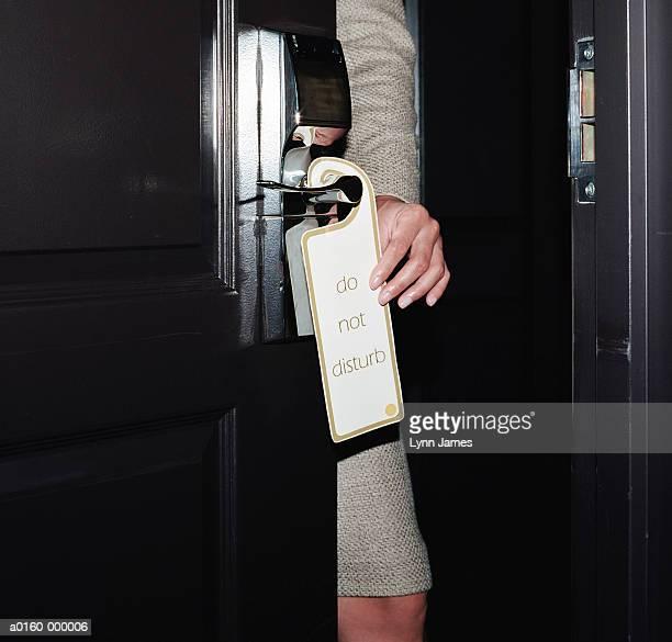 Woman Hanging Sign on Door