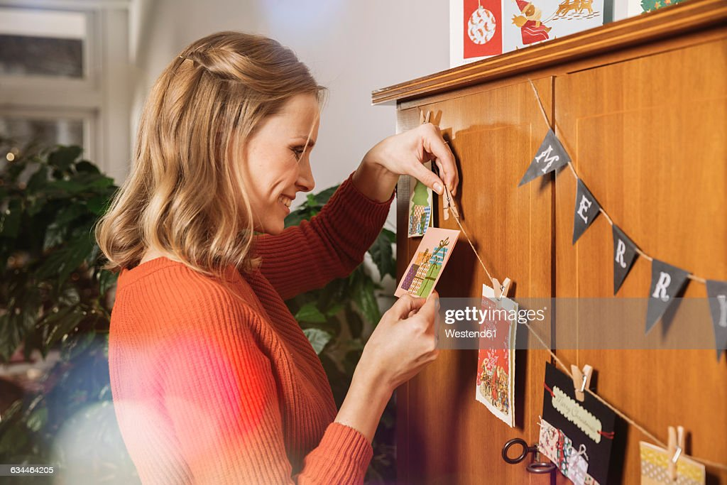 Woman hanging up Holiday cards for decoration : Stock Photo