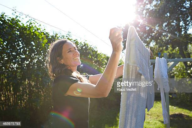Woman hanging up laundry in her garden at sunset