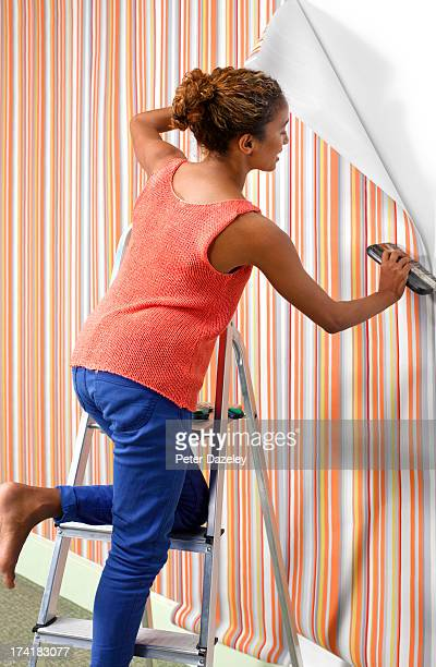 woman hanging wallpaper - decoration stock pictures, royalty-free photos & images