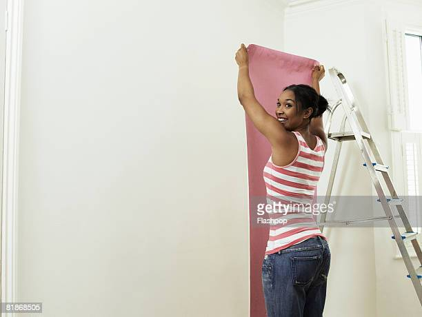 woman hanging wallpaper - hanging stock pictures, royalty-free photos & images