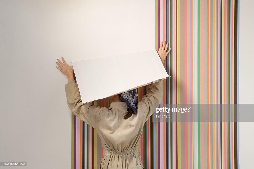 Woman hanging wallpaper, rear view : Stock Photo
