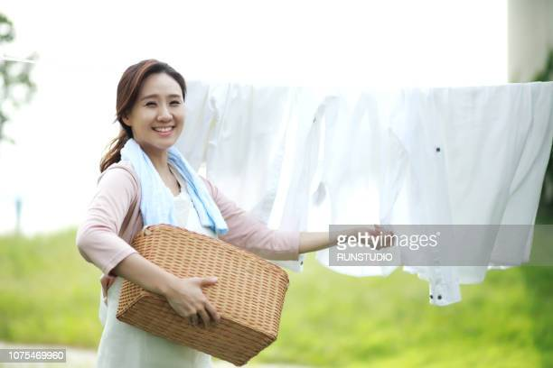 woman hanging washing on clothesline, portrait - stereotypical homemaker stock pictures, royalty-free photos & images