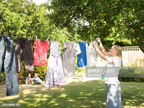 Woman hanging washing on line, children (5-7) in background