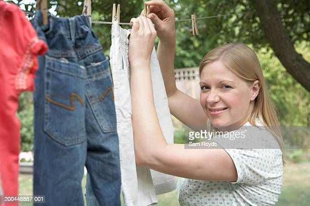 Woman hanging washing on line, close-up, portrait
