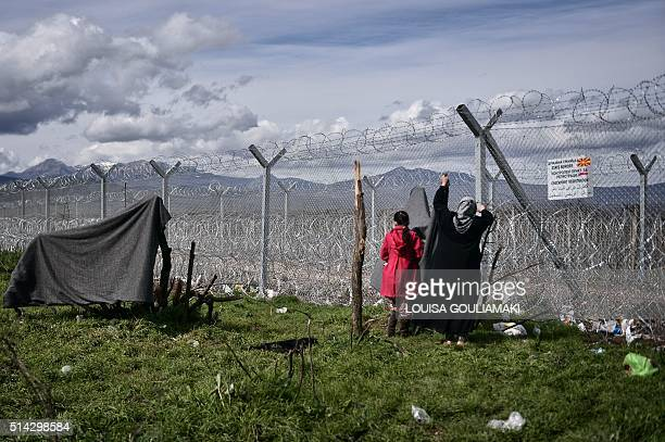 A woman hangs a blanket at the border fence of the Greek Macedonian borders near the village of Idomeni on March 8 where thousands of refugees and...
