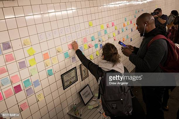 A woman hangs a postit note on a wall at the 6th Avenue subway station as part of a public art project entitled 'Subway Therapy' November 10 2016 in...