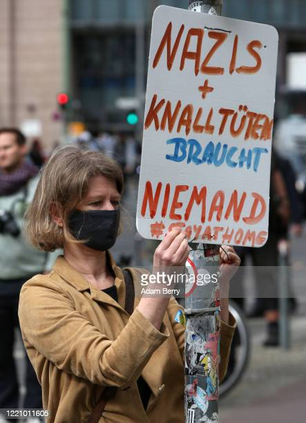 Woman hangs a sign calling on protesters demonstrating against restrictions on public life designed to stem the spread of the coronavirus, or...