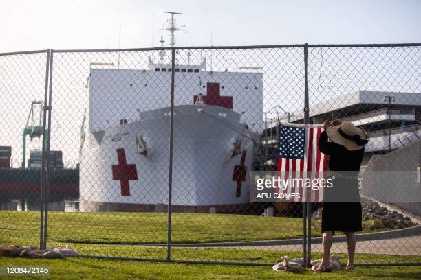 A woman hangs a US flag in a fence in front of the US Navy Hospital ship Mercy on March 28 2020 at the Port of Los Angeles in the city of San Pedro...