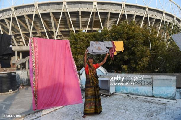 A woman hangs clothes for drying outside the Motera stadium the world's largest cricket stadium on the outskirts of Ahmedabad on February 12 2020