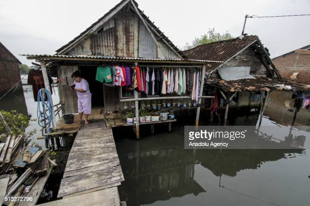 A woman hangs clothes in front of a waterlogged home in Sriwulan village Sayung subdistrict of Demak regency Central Java Indonesia on February 2...