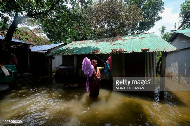 Woman hangs clothes to dry in front of her house in a flooded area due to recent monsoon rainfalls in Dhamrai on August 11, 2020.