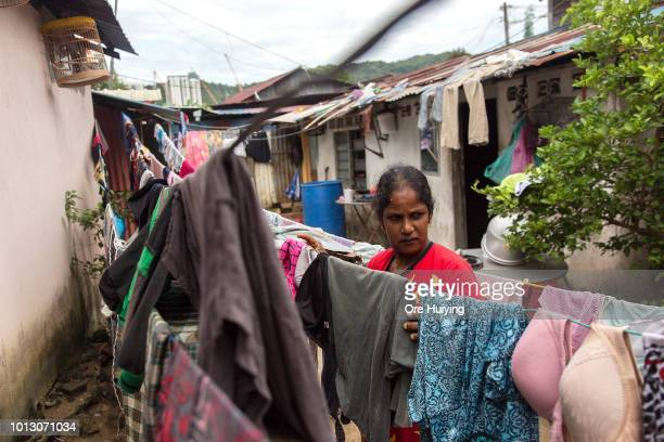 A woman hangs her clothes in a village in Kampung Pisang the site of the 234 acre land acquired by the 1MDB fund on July 31 2018 in Penang Malaysia...
