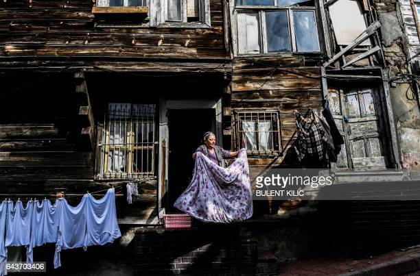 TOPSHOT A woman hangs laundry in the historical Eminonu district on February 22 2017 in Istanbul / AFP / BULENT KILIC