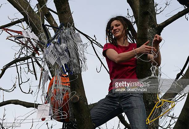 A woman hangs up hangers symbolizing illegal abortion in a tree as demonstrators protest against a possible tightening of Polands abortion law...