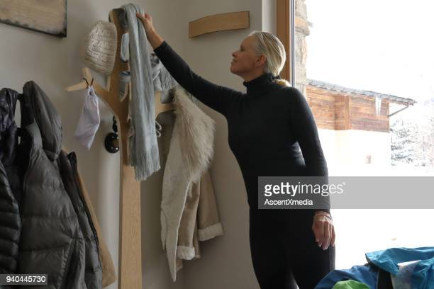 woman hangs winter clothes on wall hanger - fur jacket stock pictures, royalty-free photos & images