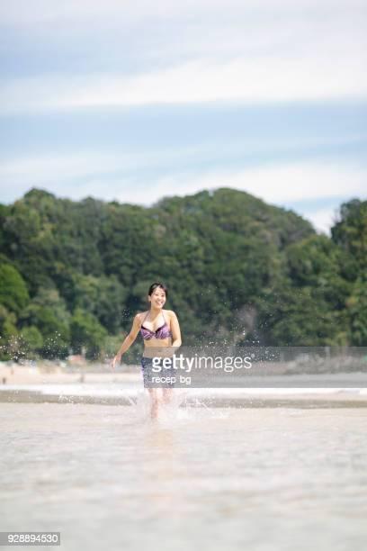 海で楽しそうに走っている女性 - 静岡市 ストックフォトと画像