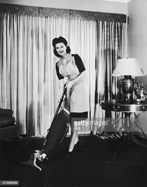 Woman happily using her Packard vacuum cleaner, circa 1948.