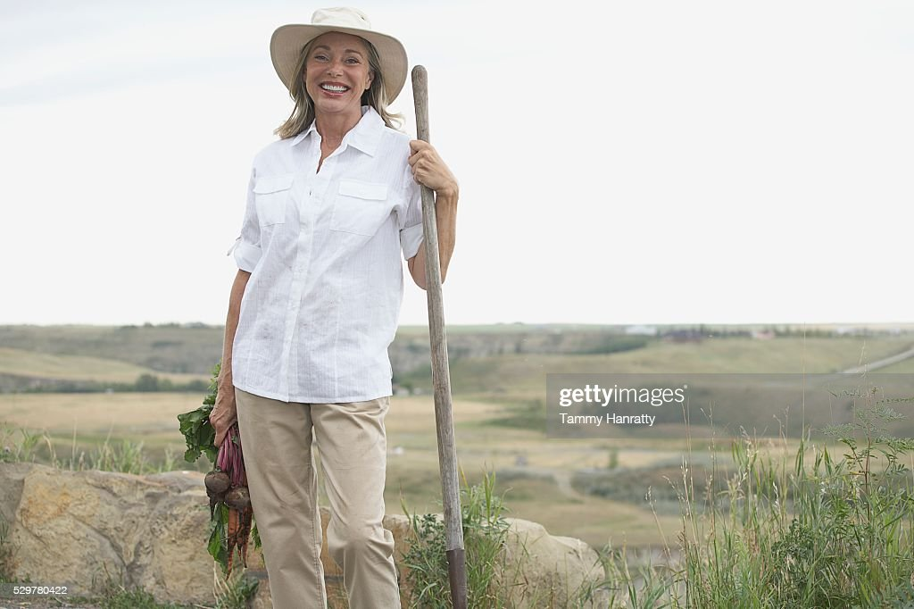 Woman harvesting vegetable from garden : Stock Photo