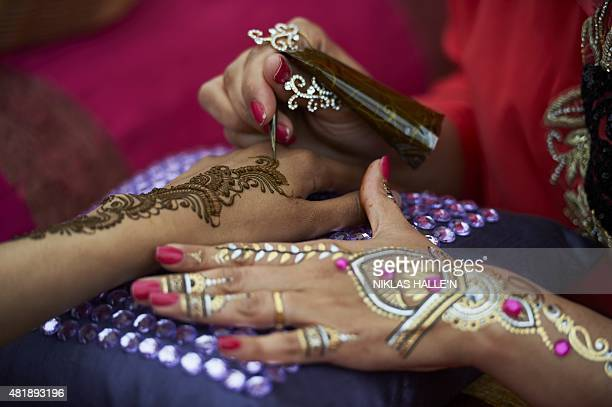 A woman has a henna tattoo painted onto her hands during Eid festival celebrations in London's Trafalgar square marking the end of the muslim holy...