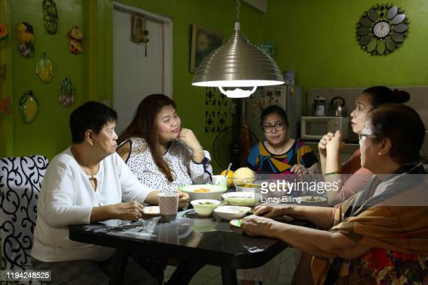a woman has a meal with her family - daily life in philippines stock pictures, royalty-free photos & images
