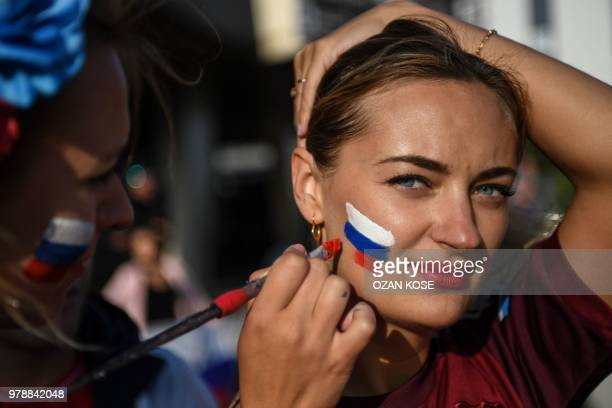 A woman has a Russian national flag painted on her cheek before the Russia 2018 World Cup Group A football match between Russia and Egypt at the Fan...