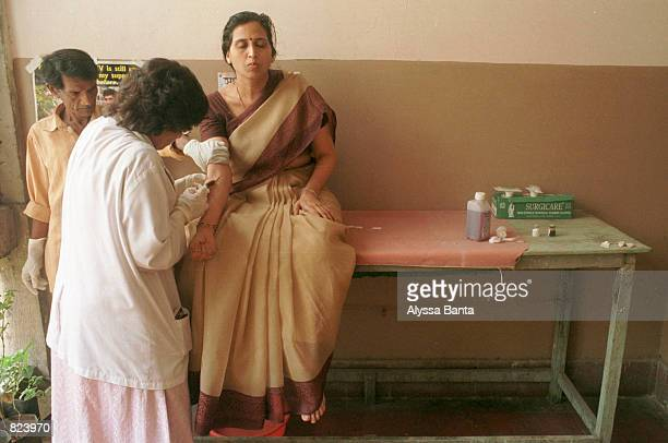 A woman has blood drawn from her arm to test for HIV after her husband has begun to show symptoms of the disease February 20 2001 at the J J Hospital...