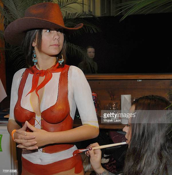 A woman has body paint applied at the Moscow exhibition hall during the Millionaire Fair October 28 2006 in Moscow Russia Private wealth was banned...