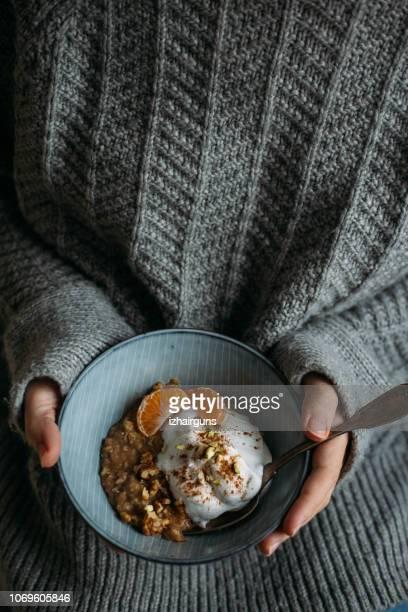 女は果実、ナッツとおいしい乳糖無料ベジタリアン ヨーグルトとグルテン フリーお粥の朝食を持っています。健康的な朝の概念、寒い冬の朝。 - ポリッジ ストックフォトと画像