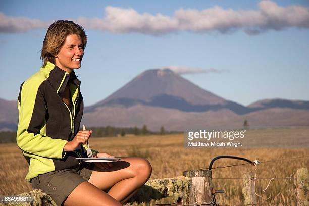 A woman has breakfast in a volcanic national park.