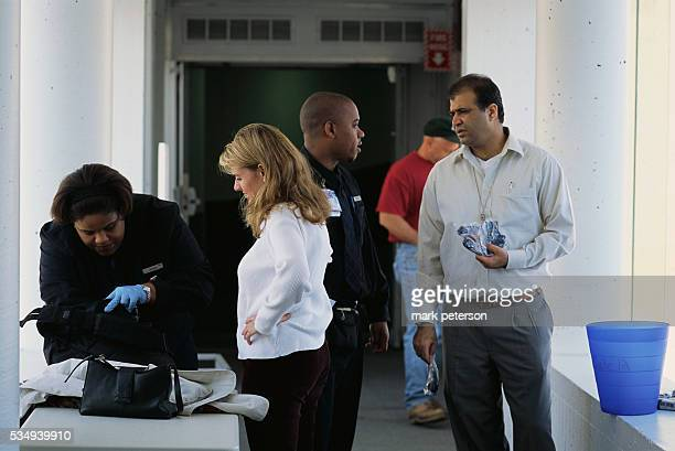 A woman has her bags searched by a security guard at a John F Kennedy International Airport security checkpoint a month after the September 11th...