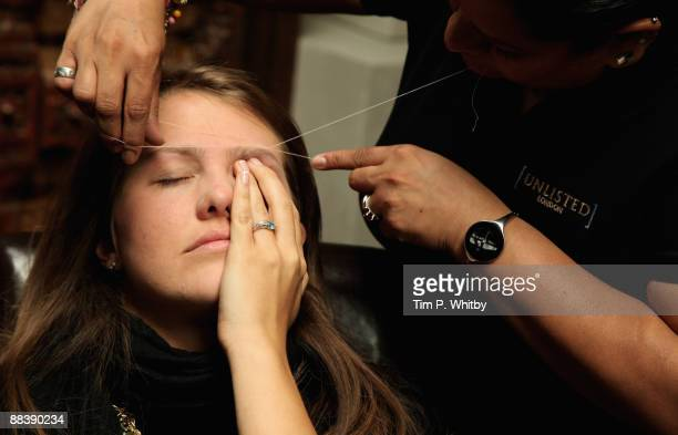 A woman has her eyebrows threaded at the Designer Couture Trunk Show hosted by Noelle Reno at The Collection on June 10 2009 in London England
