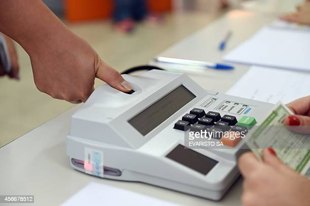 A woman has her fingerprint checked with a new biometric identification before casting her vote at a polling station in an public school in Brasilia...