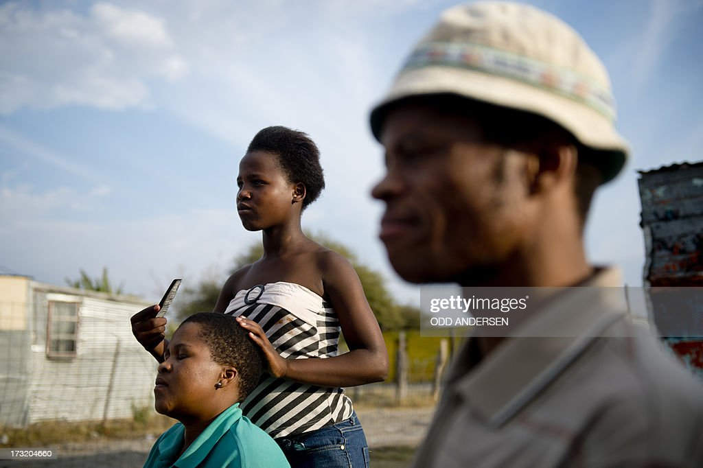 A woman has her hair trimmed at an outdoor hairdresser on July 9, 2013 in the Nkaneng shantytown next to the platinum mine, run by British company Lonmin, in Marikana. On August 16, 2012, police at the Marikana mine open fire on striking workers, killing 34 and injuring 78, during a strike was for better wages and living conditions. Miners still live in dire conditions despite a small wage increase.
