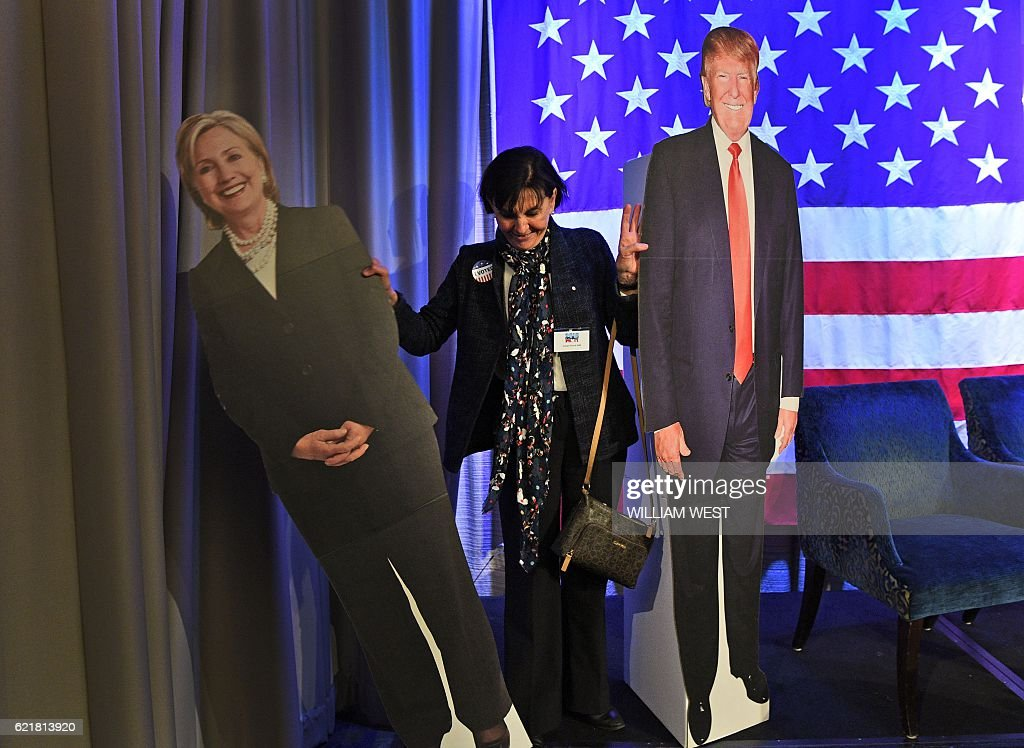 A woman (C) has her photo taken with cut-outs of presidential nominees Hillary Clinton (L) and Donald Trump at the US Consul Generals Election Watch function to watch elections results on giant screens in Sydney on November 8, 2016. US stock markets tumbled more than five percent in after-hours trading as Republican billionaire Donald Trump appeared poised to defeat Democratic rival Hillary Clinton in the race for the White House. / AFP / WILLIAM