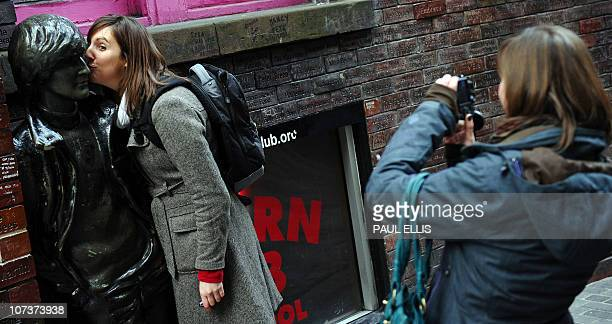 A woman has her photograph taken as she pretends to kiss the statue of a young John Lennon in Mathew Street in Liverpool northwest England on...