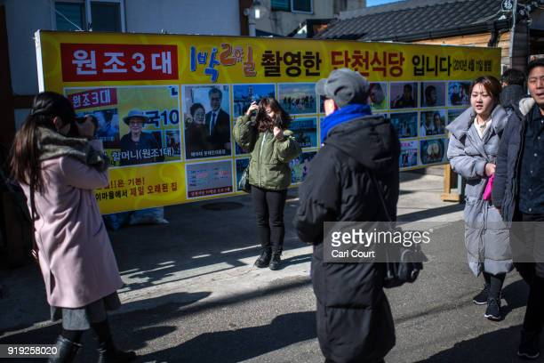 A woman has her photograph taken next to a banner advertising a television cookery program that was filmed in Abai Village on February 17 2018 in...
