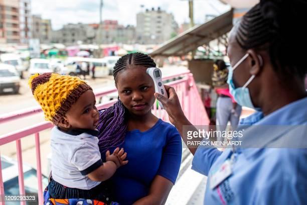 Woman has her temperature measured at Penda Health Clinic Umoja II in Nairobi, on April 6, 2020. - Suspected COVID-19 coronavirus cases are referred...